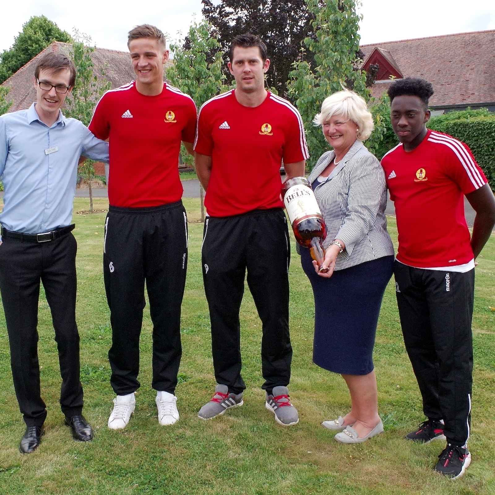 United players present a gallon bottle of whisky to local charity