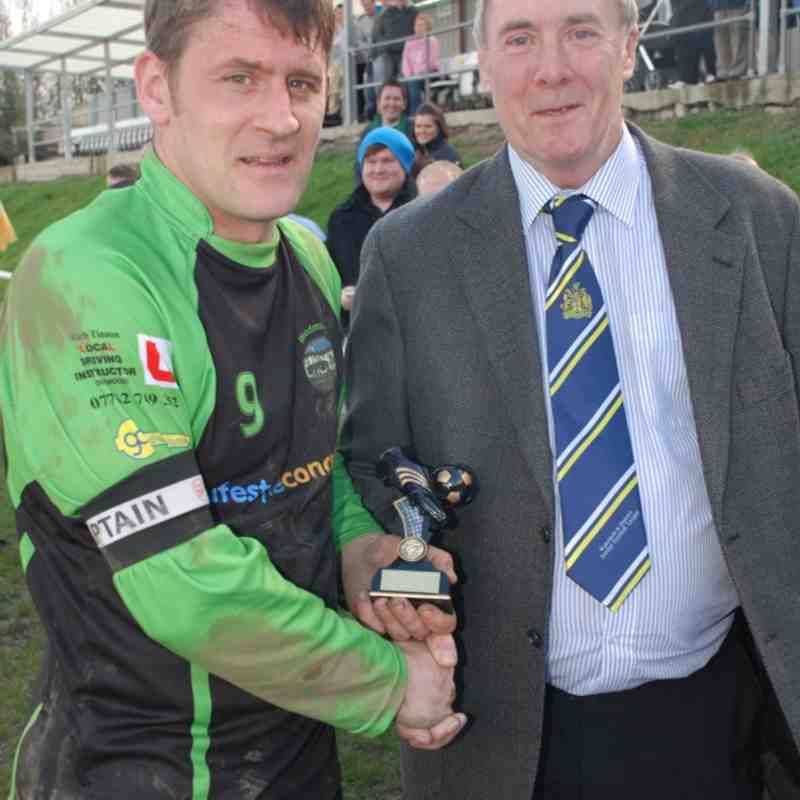 Woodman hat-trick hero Stu Bateson accepts his Man-of-the-Match award from League Management Committee member Mr. Chris Grace.
