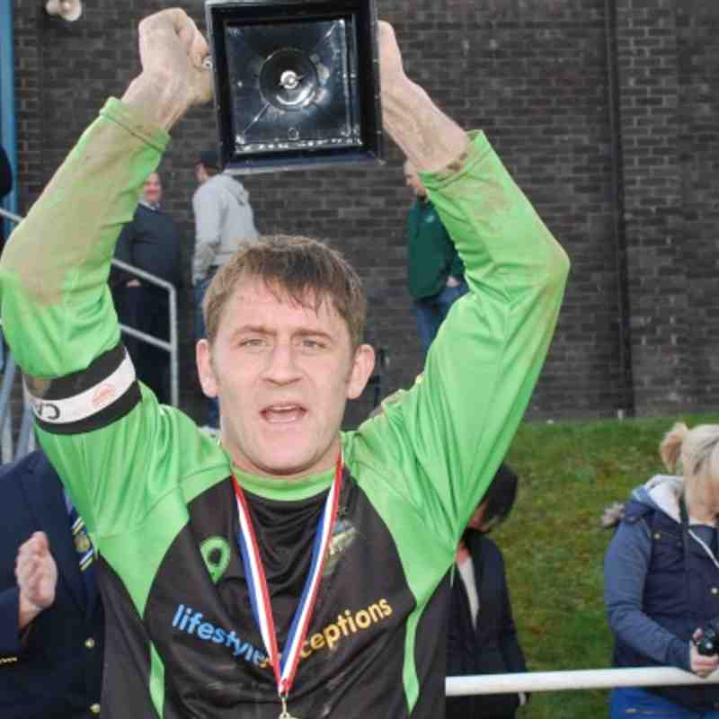Woodman skipper and hat-trick hero Stu Bateson celebrates with the Division Four League Cup.