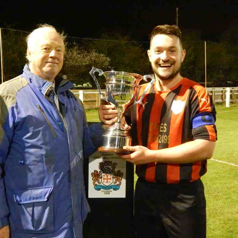 Captain Tom Large receives the cup from Mac Webb MBE