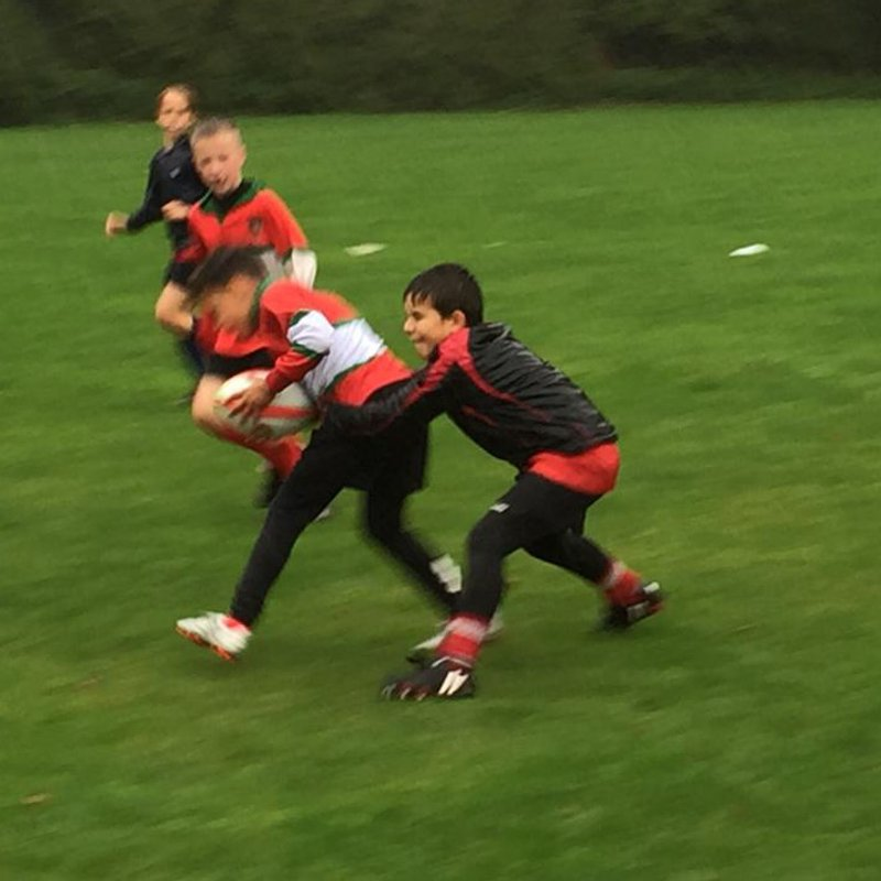 U9 having fun tackling in the rain