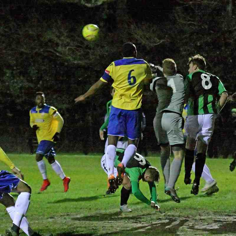 Burgess Hill keeper Josh James punches clear from Stanley Muguo (yellow no 6)