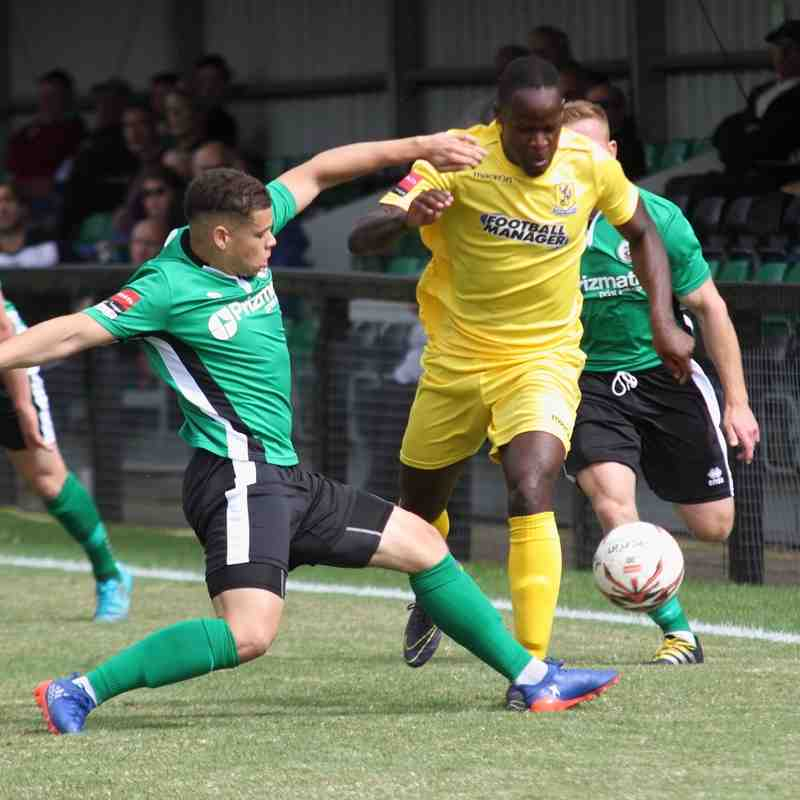 Burgess Hill's Joey Taylor (green) tackles Nigel Neita