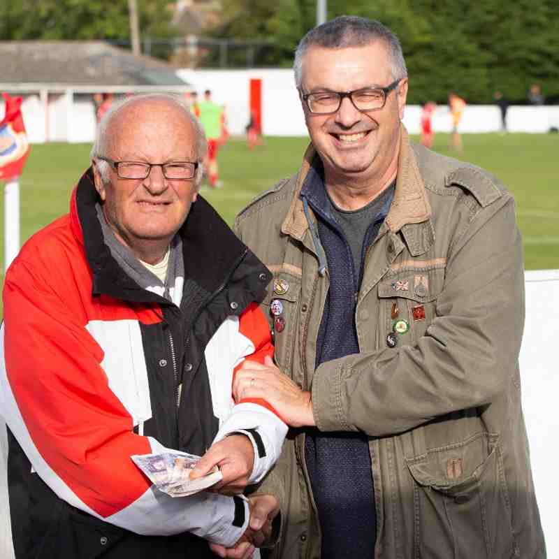 George Corney receives his winnings from the supporters fund draw at half time